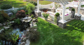 koi pond and sitting area with stone pillars and pergola