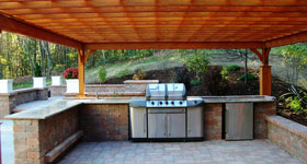 outdoor kitchen with pergola and large wrap around brick bar
